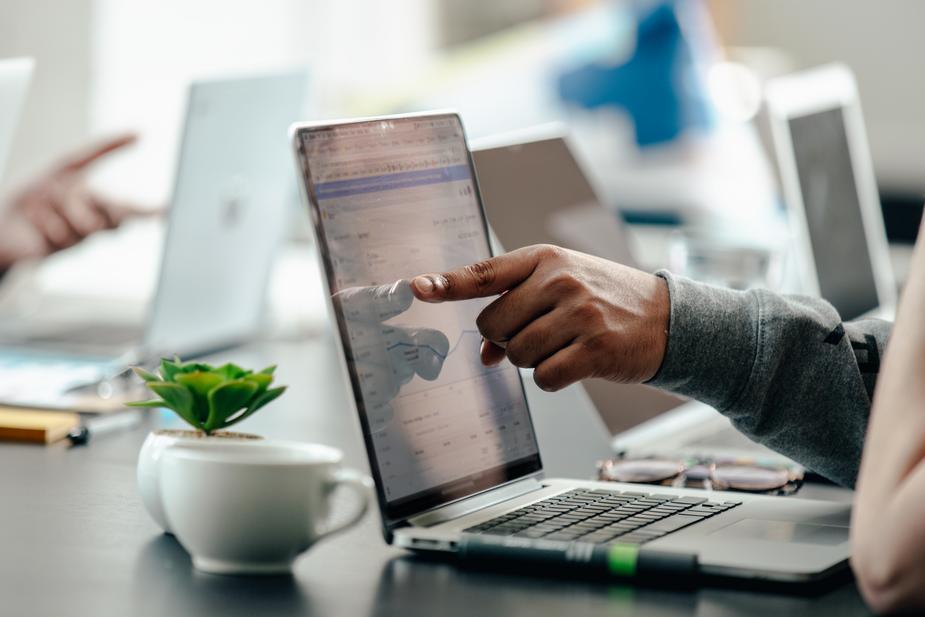 man pointing at laptop screen analytics